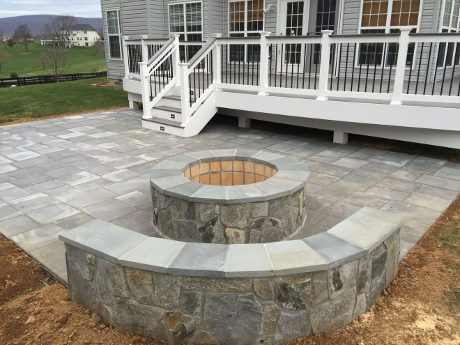 a beautiful paver patio with stone seating walls and a fire
