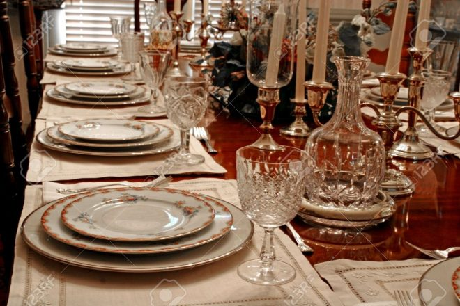 a formal dining table set with china crystal and candles