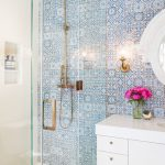 a glass shower stall lets blue and white spanish style tile