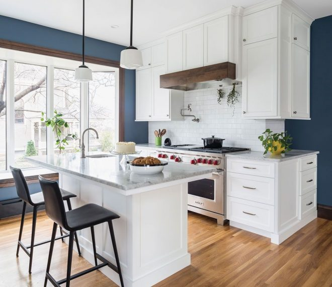 a kitchen with wood flooring white cabinetry stainless steel