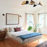 a minimal bohemian bedroom with big windows and bright