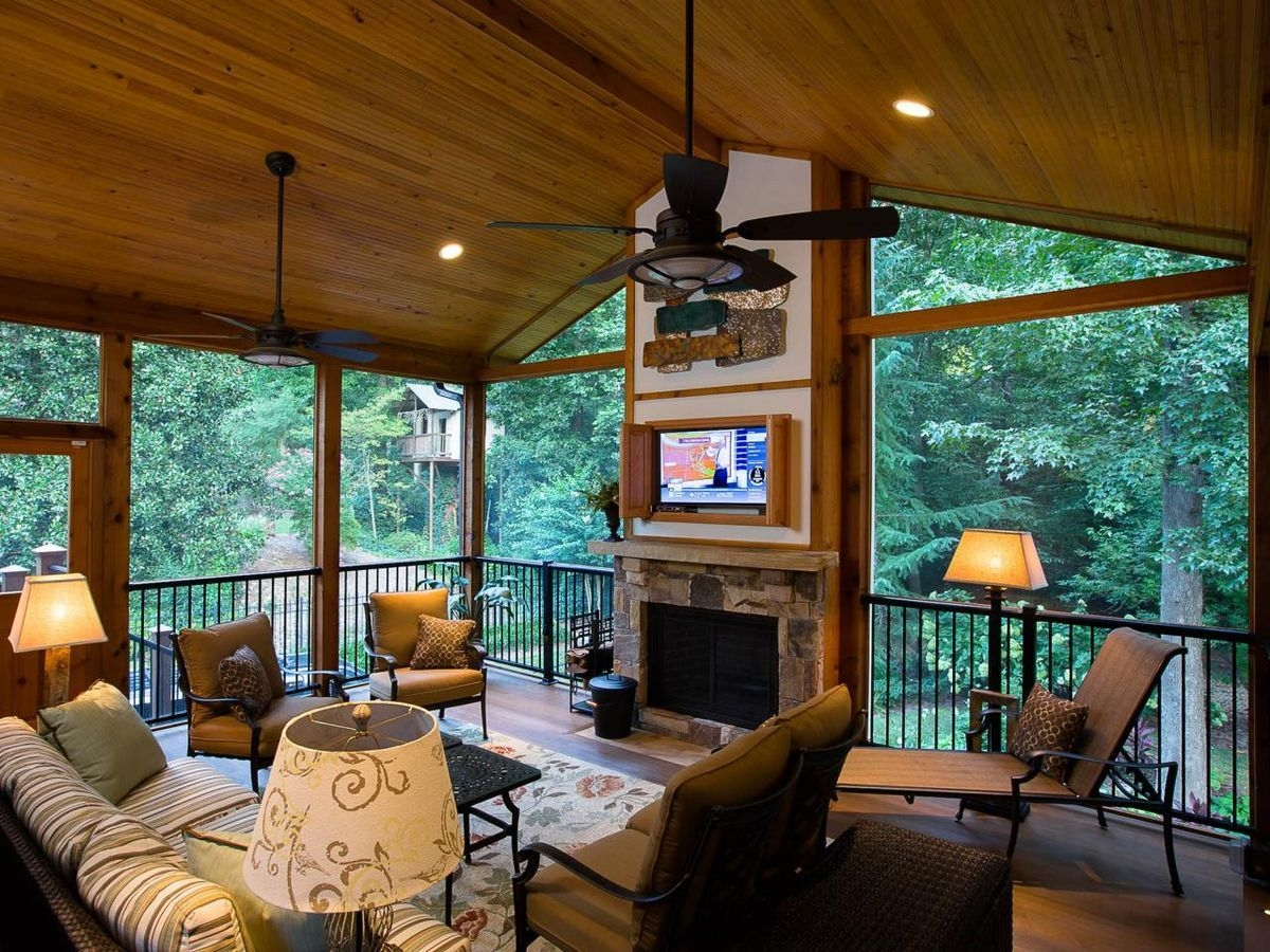 a rustic covered porch with a fireplace and tv screen centerpiece