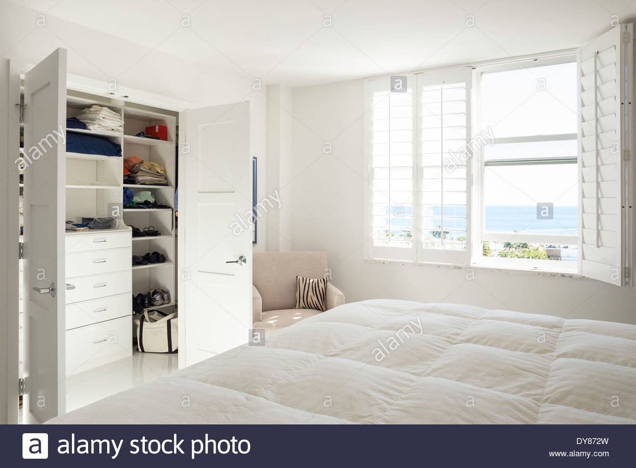 all white sunny bright showcase master bedroom with built