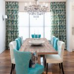 alternating turquoise and white chairs surround a long