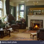 antique mirror above fireplace with lighted fire in country living