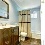 bathroom with brown tile floor and light blue walls stock image