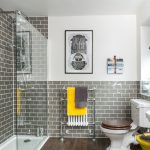 bathroom with grey tiles and yellow accents yellow