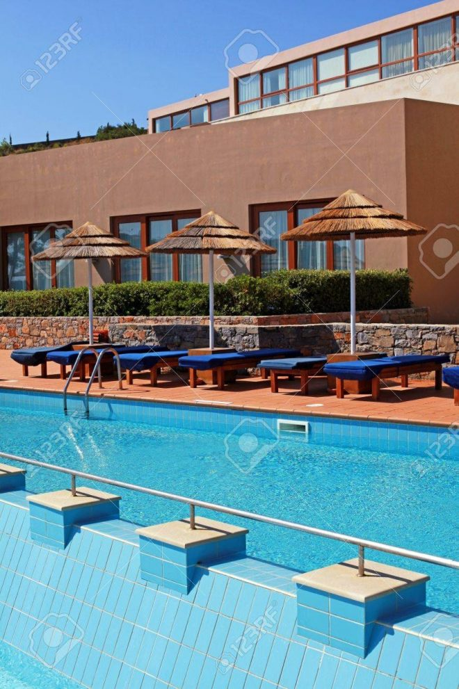 beautiful outdoor poolside with pool bed and umbrella in summer