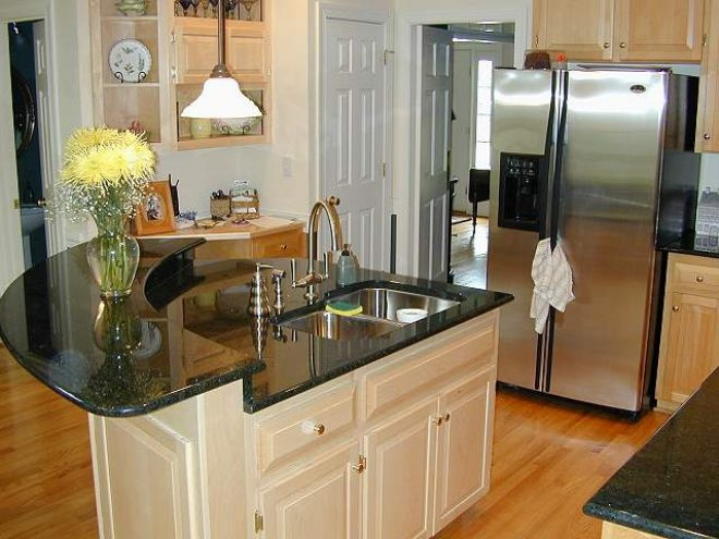 beige wooden curved kitchen island with black granite top and