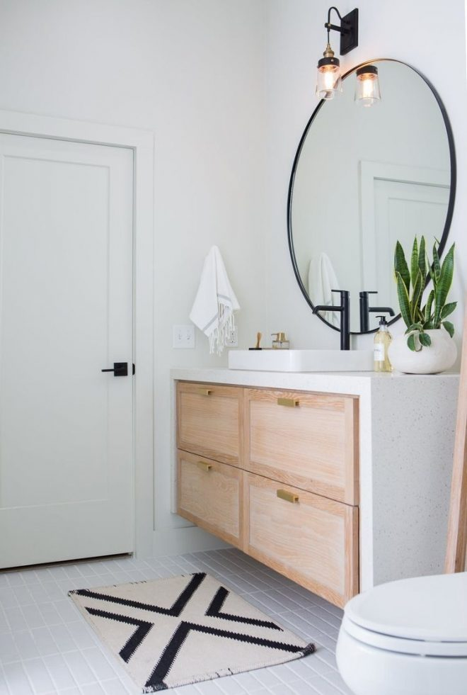 big round mirror in bathroom with white oak vanity and white