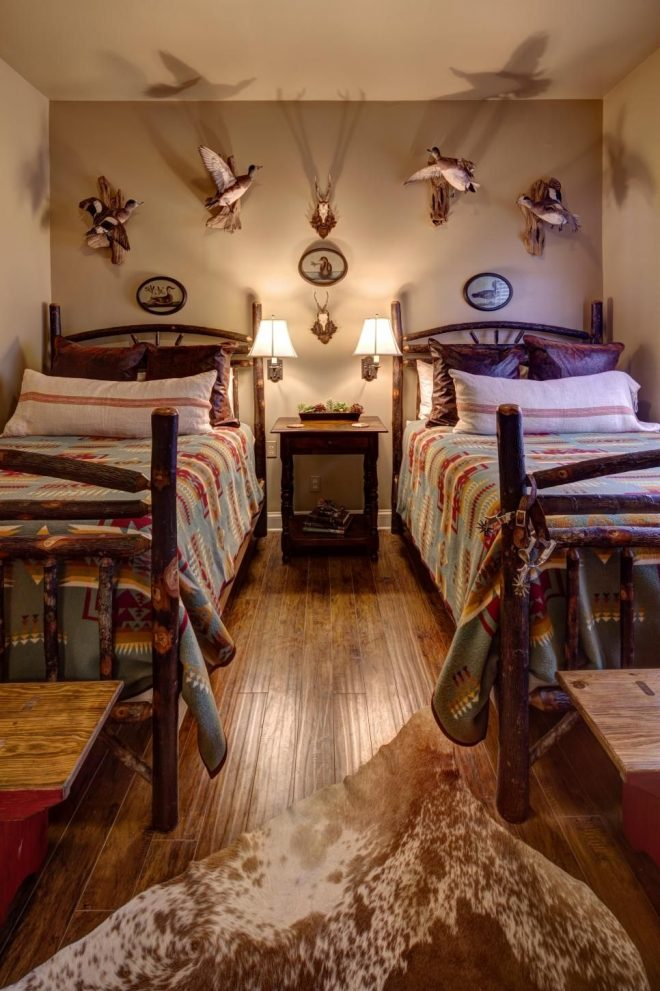 birds are mounted on the wall behind two log beds in this lodge