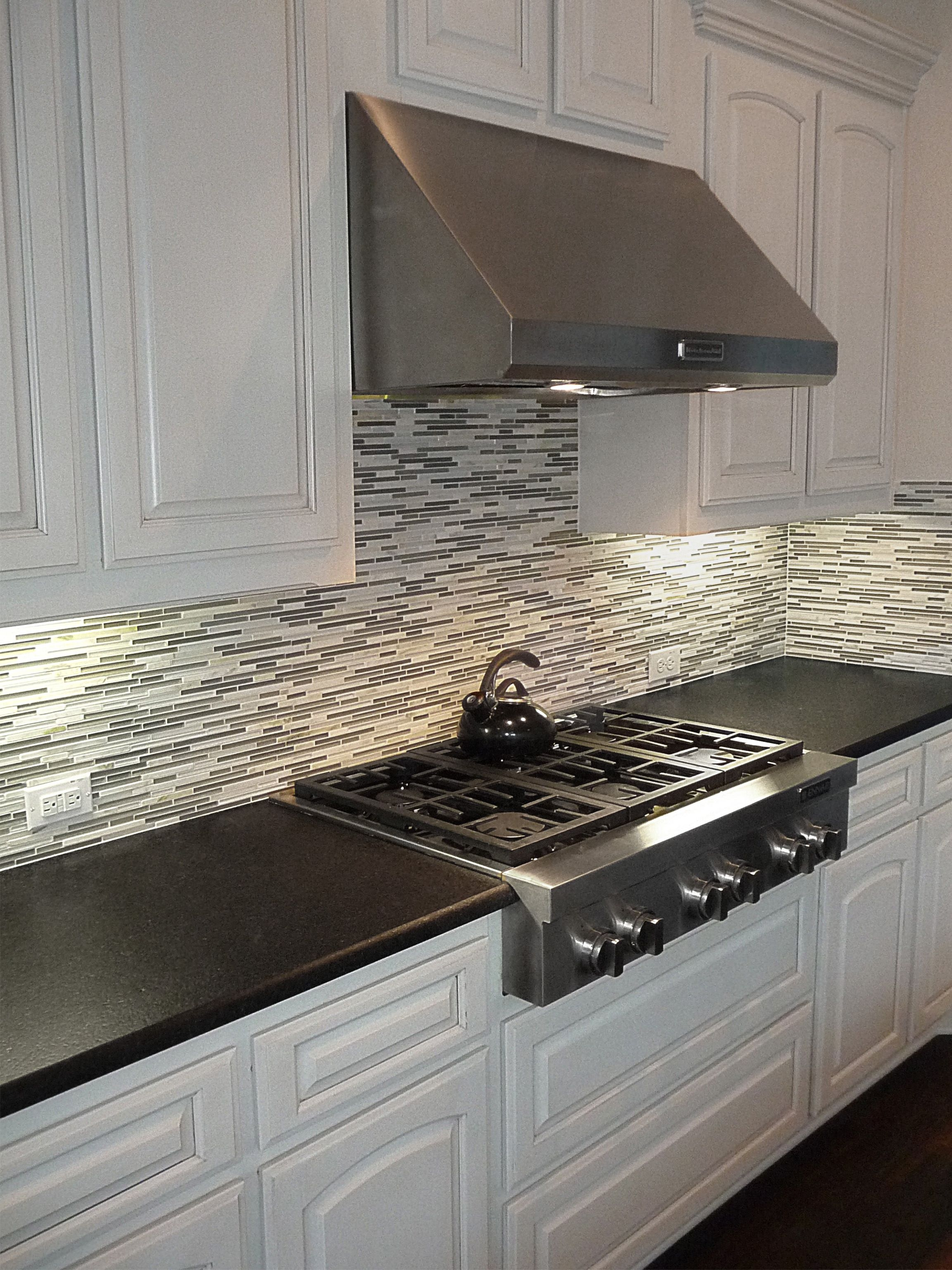 black pearl leather granite countertops with a mosaic backsplash and