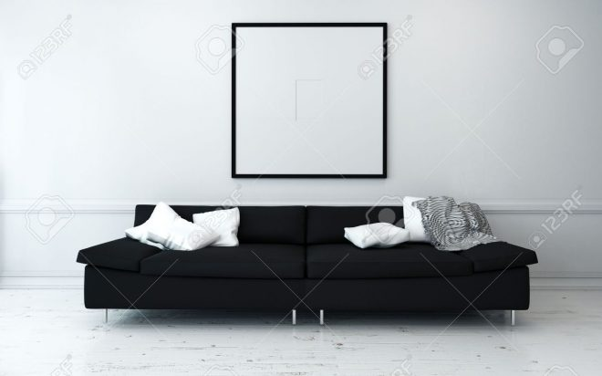 black sofa with white cushions in sparsely decorated modern living