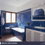 bright blue tiles on wall above bath in modern spanish bathroom