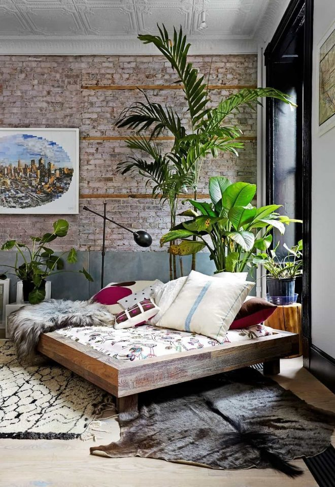 bright tropical bedroom with wall mirror and palm tree houseplant