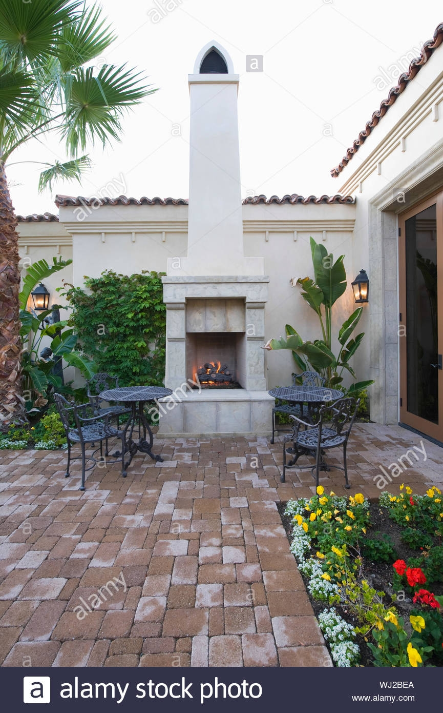 chairs and tables at outdoor fireplace in courtyard garden