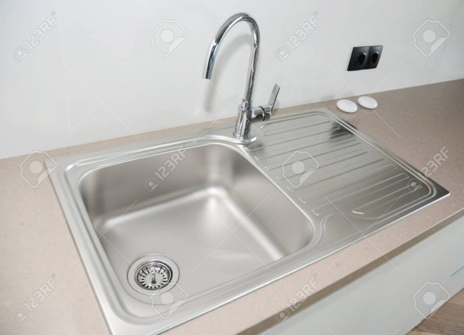 close up on modern kitchen metal faucet and metal kitchen sink