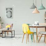 colorful lamps above wooden table and chairs in yellow living