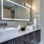 contemporary master bathroom features a dark vanity cabinet fitted