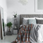 cozy interior of a monochromatic bedroom with a king size bed