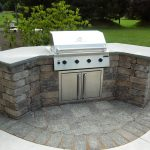 curved stone prefab kitchen island with gray concrete