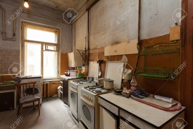 dirty kitchen with furniture and gas stoves is in the apartment