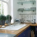 double white sink below window in modern kitchen with glass shelves