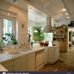 double white sinks below window in openplan white fitted galley