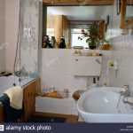 engraved glass panel on bath in small white bathroom with