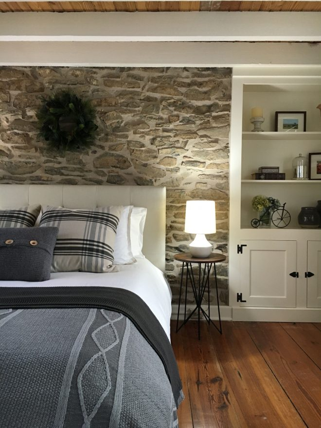 exposed original stone accent wall behind the headboard