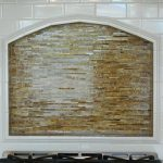 framed arched kitchen niche behind cooktop with stacked