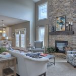 great room with 2 story ceiling gas fireplace with stone