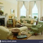 green armchair and sofa piled with cushions in traditional