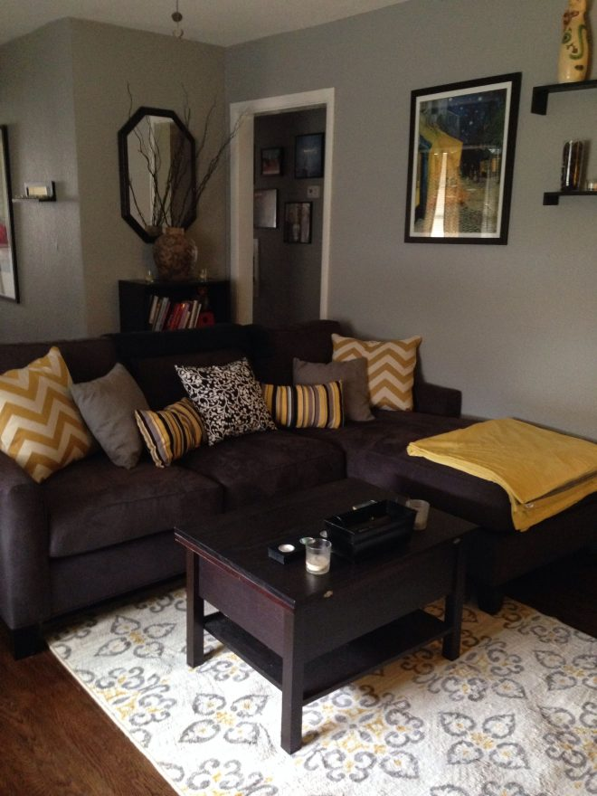 grey and yellow living room with dark couch possible