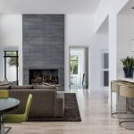 grey slate fireplace with green chairs wood floors white