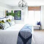 guest bedroom with woven shades ribbon trimmed drapes