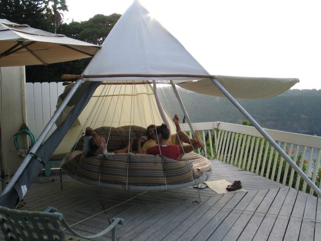 hanging a floating bed on a deck creates extra sleeping room