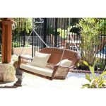 honey resin wicker porch swing with ivory cushion