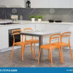house interior in kitchen white and grey with orange seat
