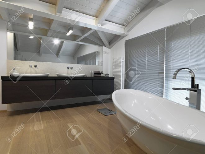interiors shots of a modern bathroom in the attic room with wooden