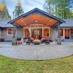 large back yard with grass and covered patio with firepit