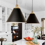 large black and gold pendant lights over white marble