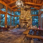 large screen porch with stacked stone fireplace log cabin