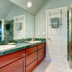 light green bathroom with vaulted ceiling tile floor and brown