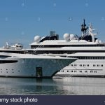luxury yacht with private helicopter moored on harbor stock