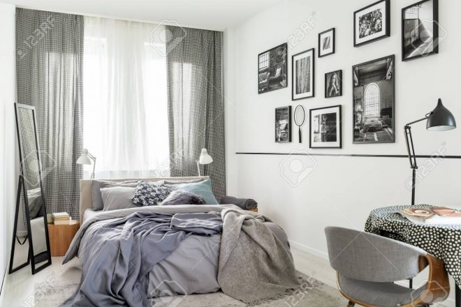 mirror next to bed in bright grey bedroom interior with window