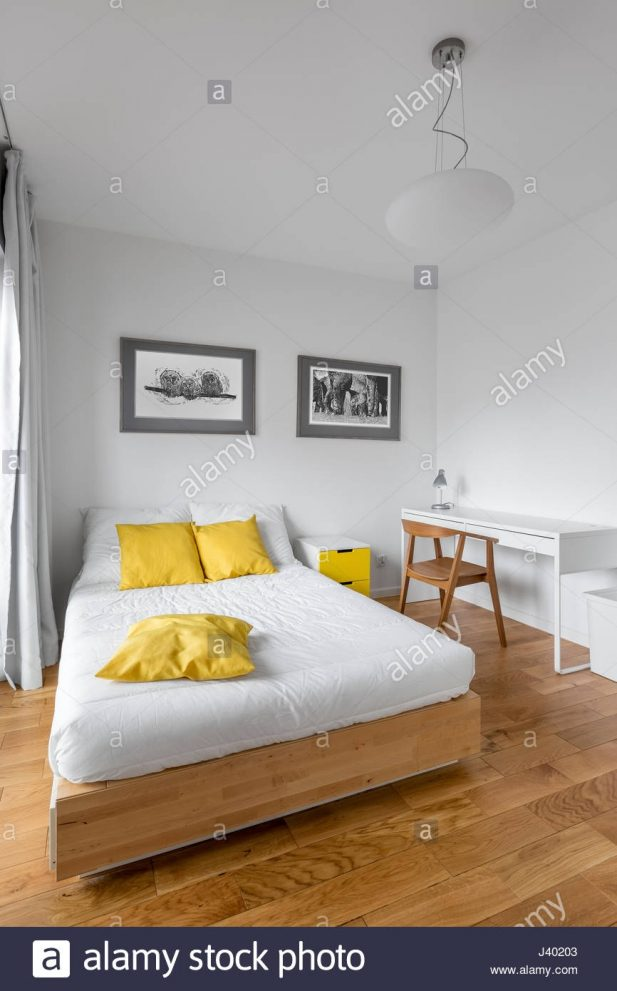 modern white bedroom with big wooden bed desk and yellow