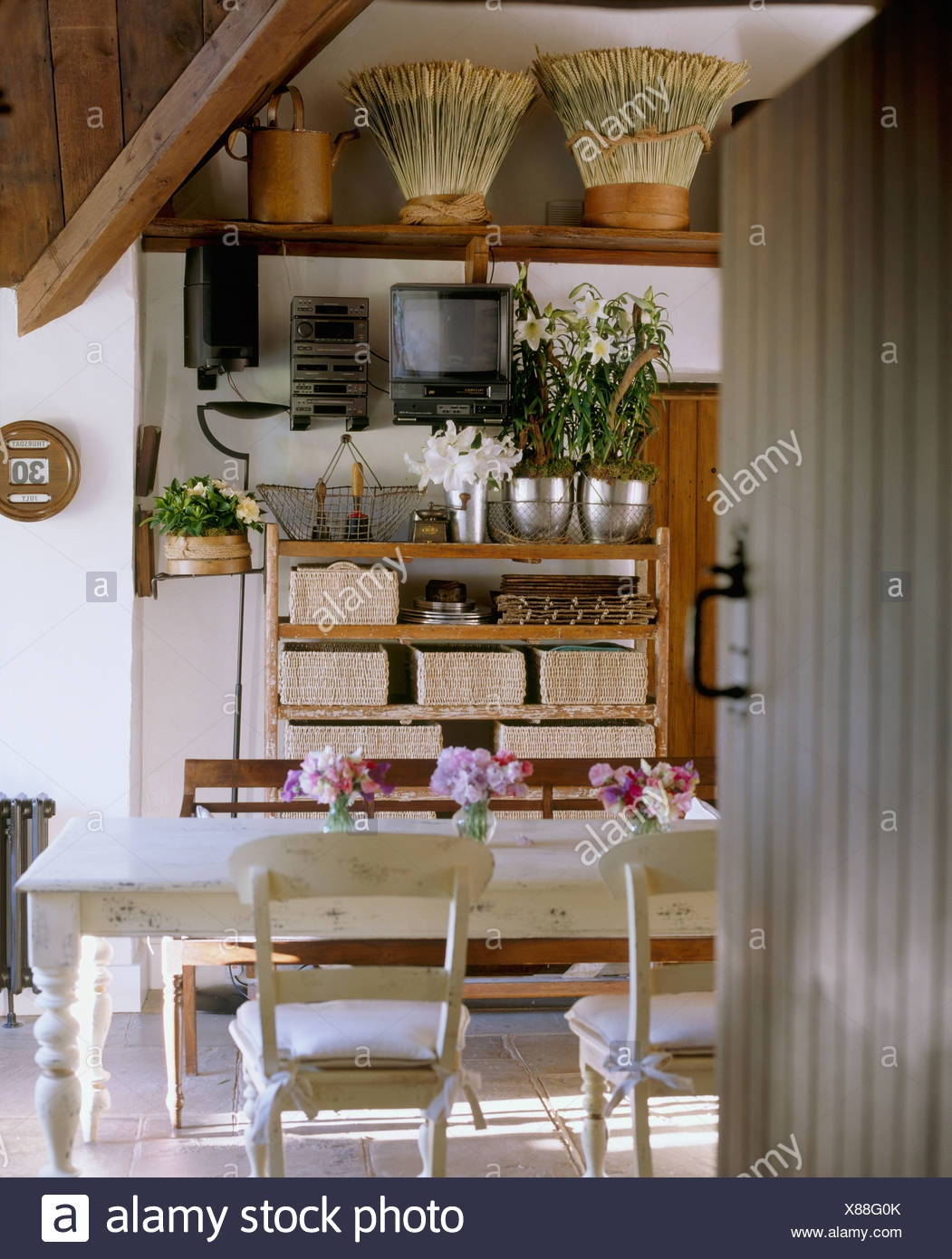 open door to country kitchen with white painted table and