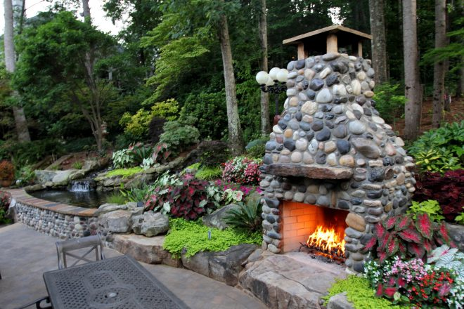 outdoor fireplace made out of montana river rock and a koi