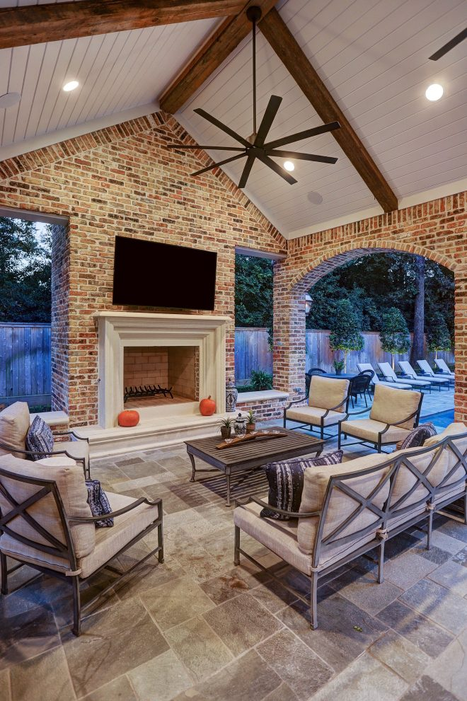 outdoor living room with cast stone fireplace vaulted
